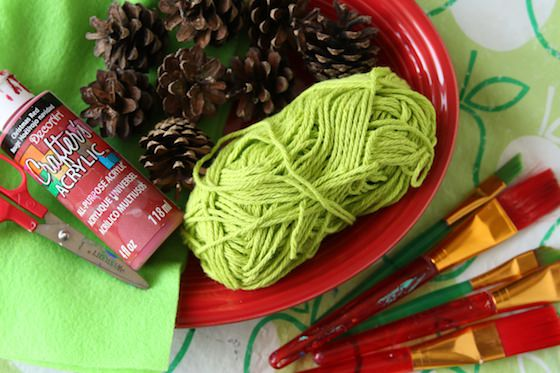 pinecones, yarn and red paint on green apple table cloth