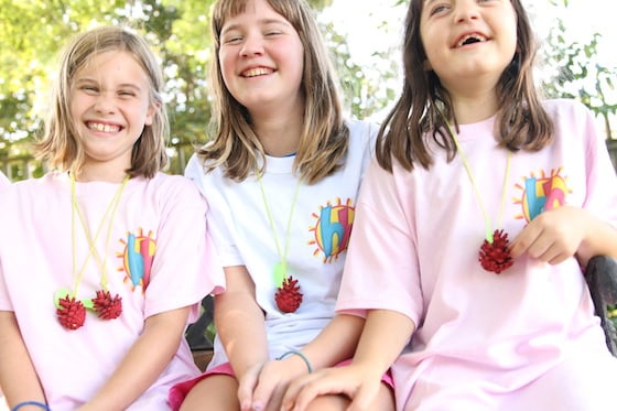 3 girls wearing pinecone apple necklaces