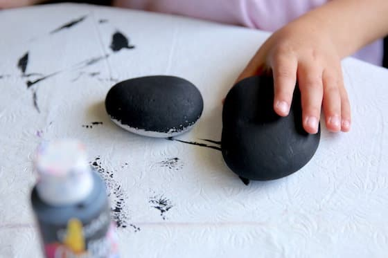 Child painting beach stone with black acrylic paint