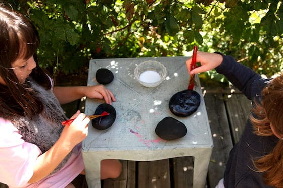 Kids varnishing black rocks