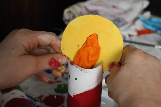 child attaching flame to paper towel roll candle