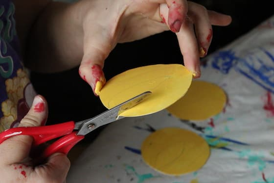 child's hands cutting yellow paper flame with red scissors