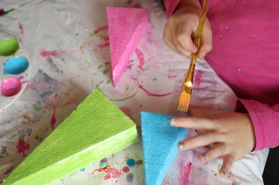 child painting styrofoam trees
