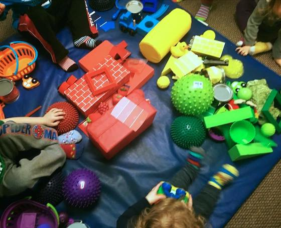 kids sitting in pile of coloured toys