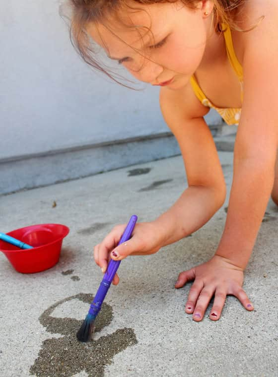 child painting sidewalk with water