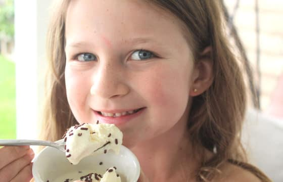 girl eating ice spoonful of homemade vanilla ice cream