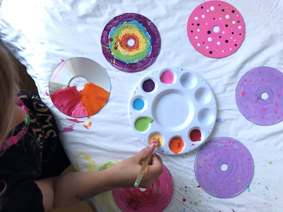 Child painting CDs with paints in paint pallet