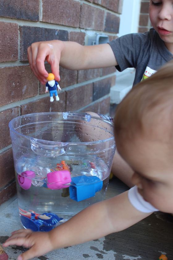 child adding toy to water for sink or float activity
