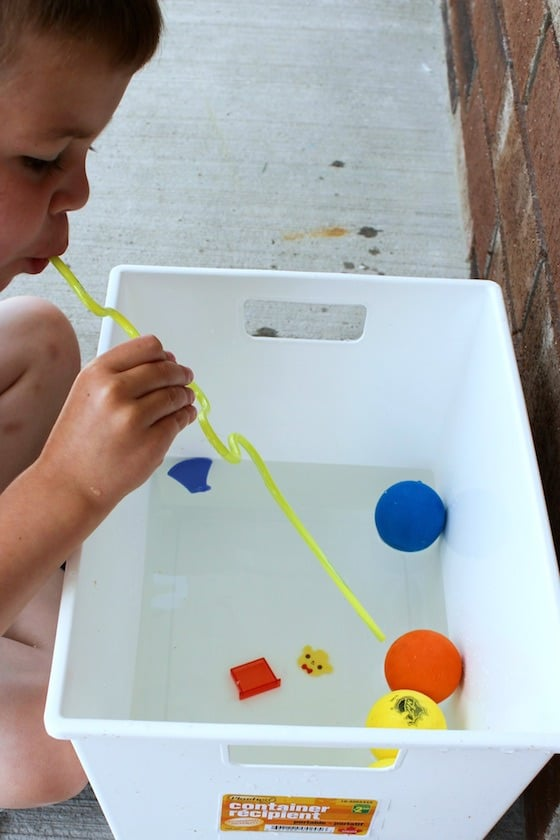 child blowing through straw to move toys on water
