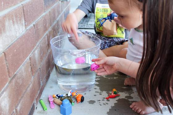 Kids adding toys to bucket of water to see if they sink or float