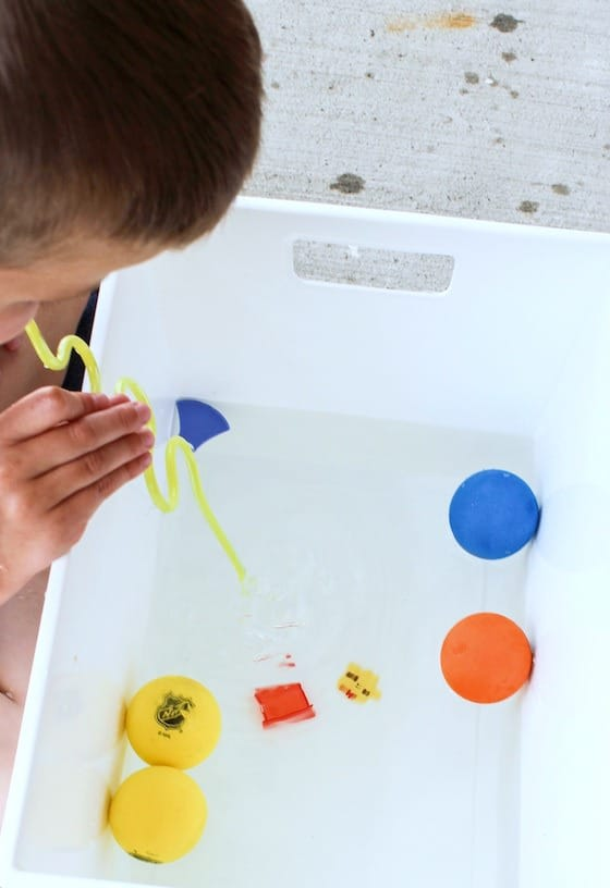 child blowing toys across water with drinking straw