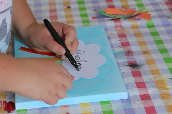 Child writing name on paper cloud