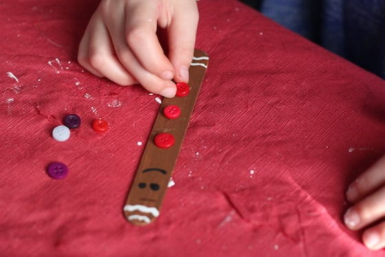 kids making popsicle stick gingerbread ornaments