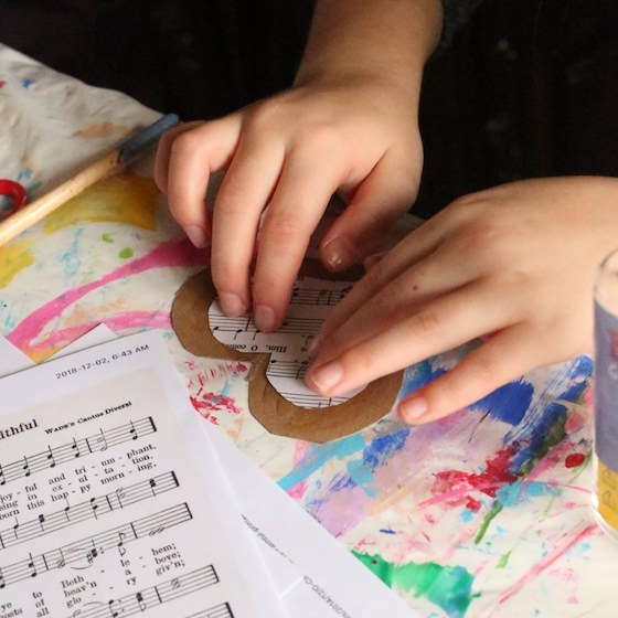 kid making cookie cutter sheet music ornament