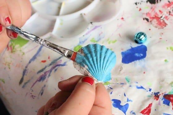 kid painting sea shell blue