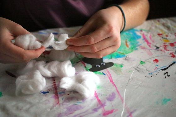 kid pulling apart cotton balls