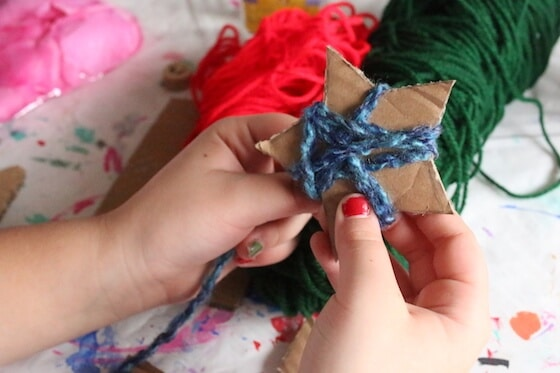 kid wrapping cardboard star in yarn