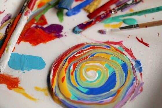 Rainbow swirls of paint on cardboard circle