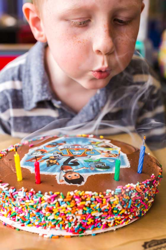 Little Boy blowing out candles on Paw Patrol cake at Chuck E Cheese