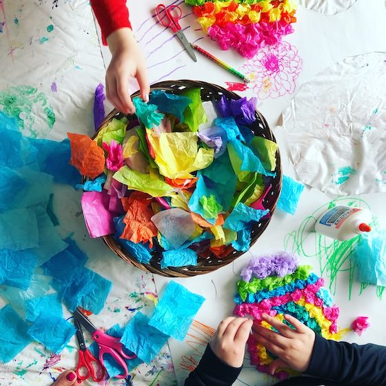 Kids reaching into basket of tissue paper scraps
