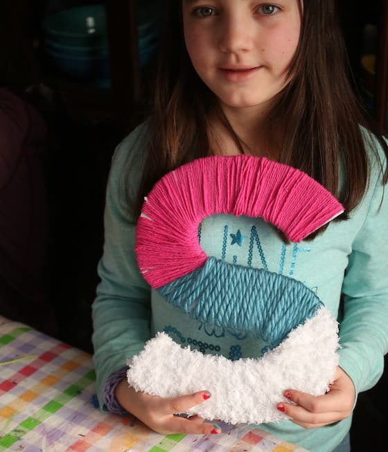 Tween holding yarn wrapped letter S