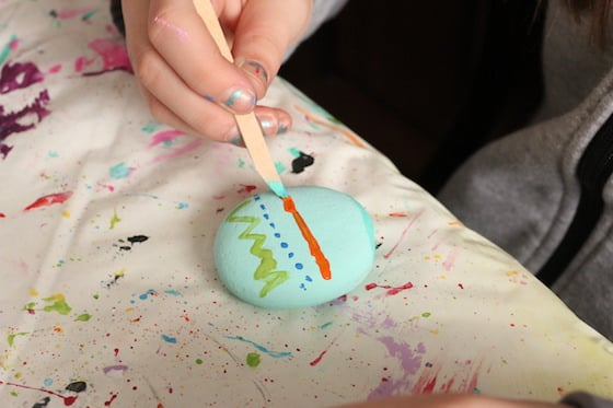 Kid painting rock to look like Easter Egg