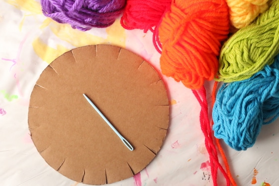Yarn, cardboard circle, sewing needle