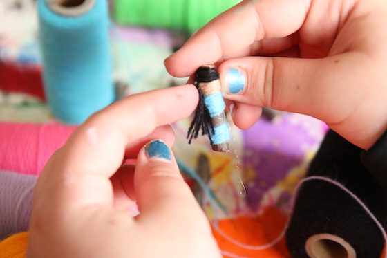 Child making a worry doll with hair