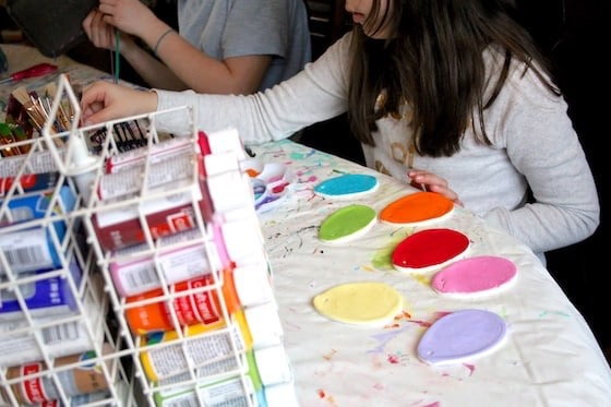Child painting clay dough eggs with acrylic paint