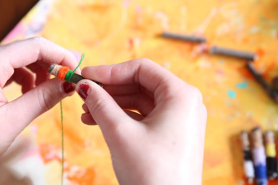 kid wrapping small twig with yarn or embroidery floss