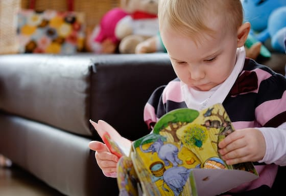 toddler looking at book from home library