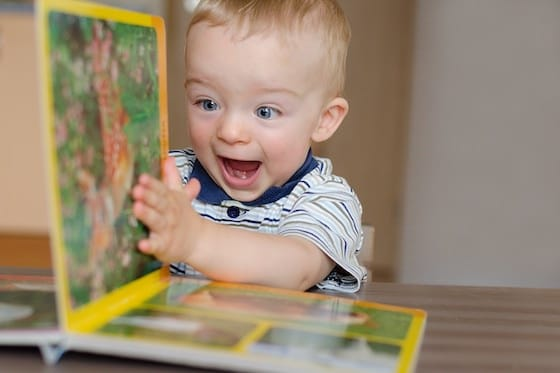 Toddler boy turning pages of book