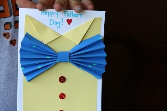 Kid holding yellow shirt and bow tie card