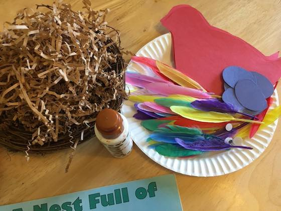 shredded paper, construction paper bird and eggs, craft feathers, googly eyes