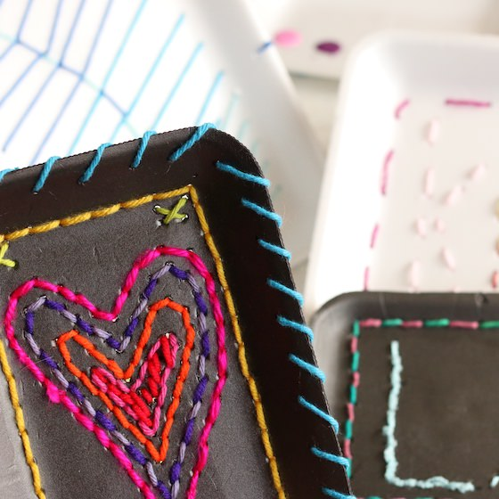 several kids sewing projects with styrofoam trays and yarn