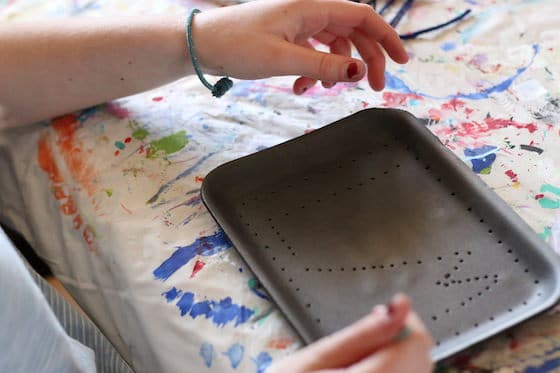 Child poking holes in styrofoam tray with pencil