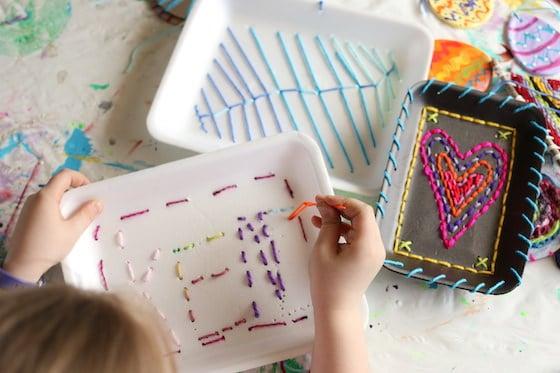 enfant cousant son nom sur un plateau de produits en polystyrène