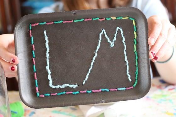 enfant pratiquant la couture des initiales sur un plateau en polystyrène noir