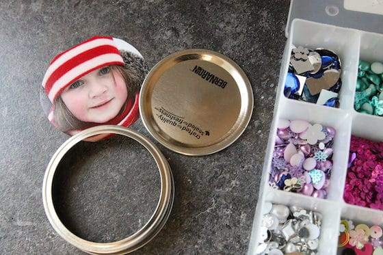 Mason jar lid, photo of child, container of beads and gems