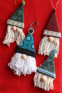 4 gnome ornaments on red background