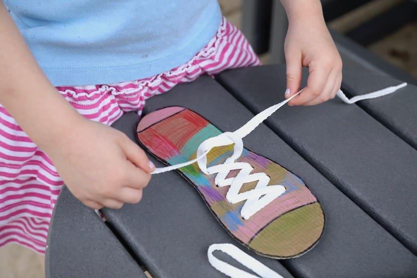 child tying shoelace on cardboard shoe