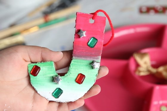 Cardboard J ornament - ombre green and red with craft jewels glued on