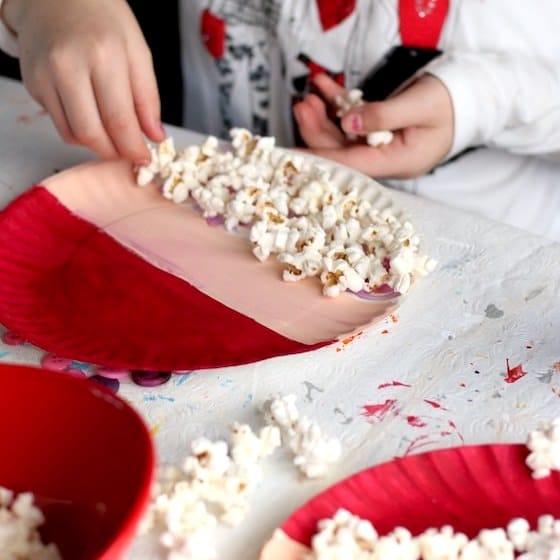 child gluing popcorn beard on paper plate santa