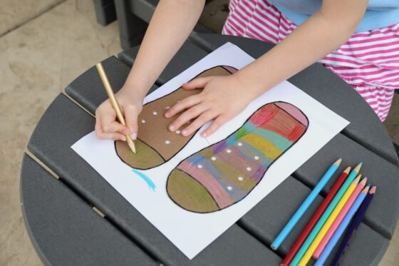 child colouring cardboard shoe