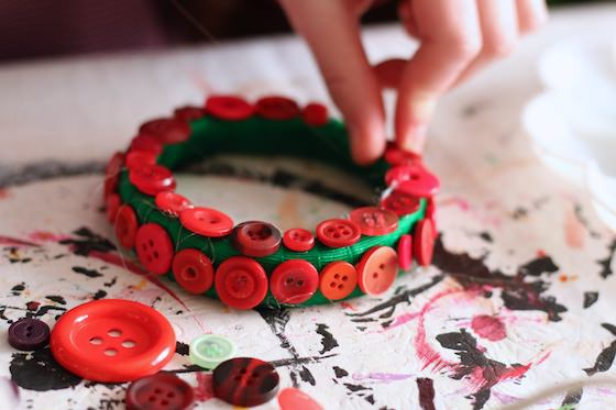 closeup kid gluing red buttons on green ribbon mason lid