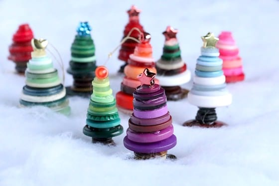 Colourful button Christmas trees standing on bed of white quilt batting