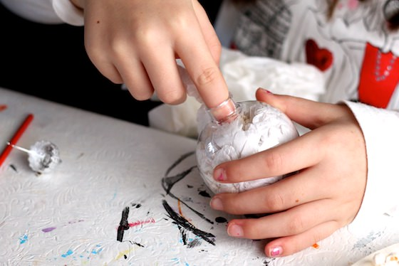 child filling clear ornament with white tissue paper