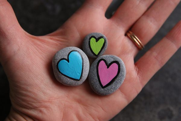 3 painted heart worry stones in palm of hand