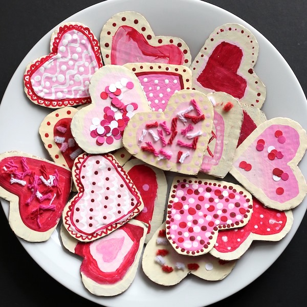 plate of cardboard heart cookies with paint icing and yarn sprinkles