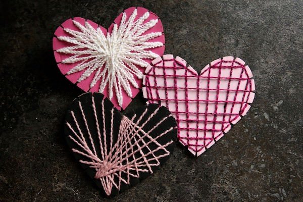 3 painted cardboard hearts strung with fine yarn.